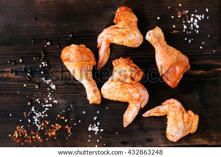 Raw Marinated chicken meat wings and legs for BBQ with seasoning salt and pepper over dark wooden background. Top view  - stock photo