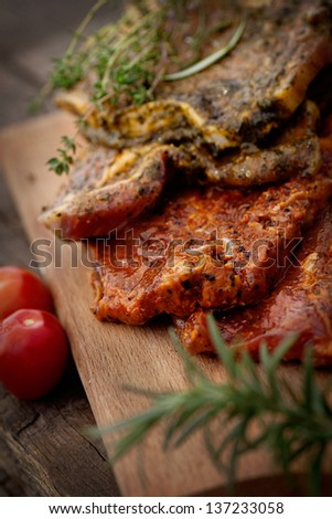 Raw marinated meat with fresh vegetables for barbecue. BBQ marinade meat - stock photo