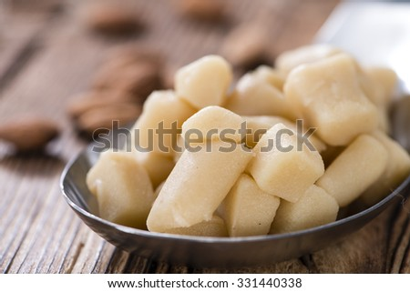 Raw Marzipan (close-up shot) with almonds on wooden background