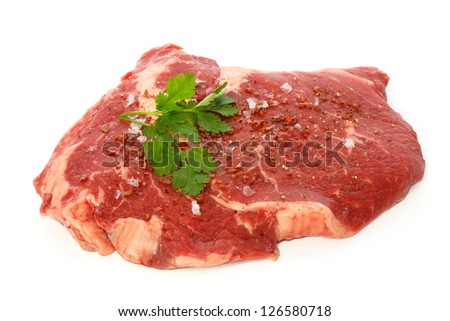 Raw matured rib eye with spices and coriander against white background - stock photo