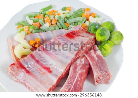 raw meat and frozen vegetables on a plate. cooking delicacies. White background. isolated
