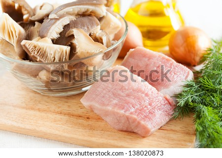 raw meat and mushrooms on the board, and other ingredients, food