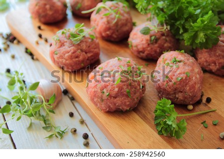 Raw meat balls with fresh parsley and herbs - stock photo