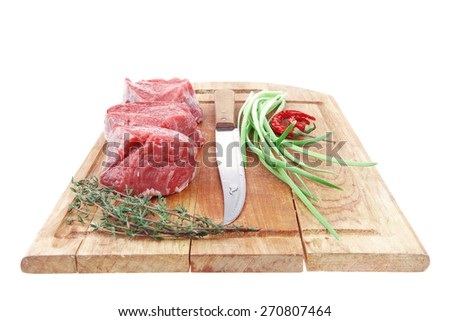 raw meat : fresh beef fillet with thyme and red hot dry pepper on wooden plate . isolated over white background - stock photo