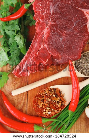 raw meat : fresh beef pork big rib piece with garlic and green stuff on wood isolated over white background - stock photo