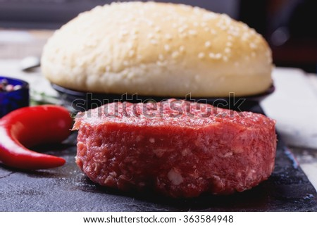 Raw meat ground burger on the black slate board ready to be cooked - stock photo