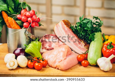 raw meat : large pieces of fresh meat, beef and pork, big rib and fillet decorated with greens and vegetables with garlic and green stuff on wood board