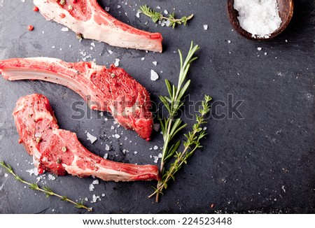 Raw meat, mutton, lamb rack with fresh herbs on a stone black background - stock photo