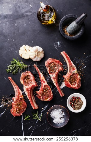 Raw meat mutton lamb ribs with herbs on black marble background - stock photo