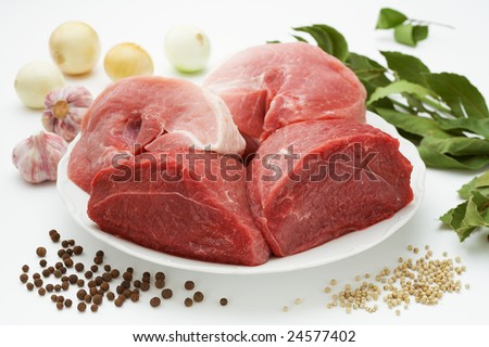 Raw meat on white plate and spices