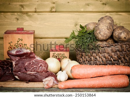 Raw meat, potato, onion, garlic, carrot and dill on wooden table. Toned. - stock photo