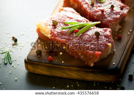 Raw meat. Raw beef steak on a cutting board with rosemary and spices. - stock photo