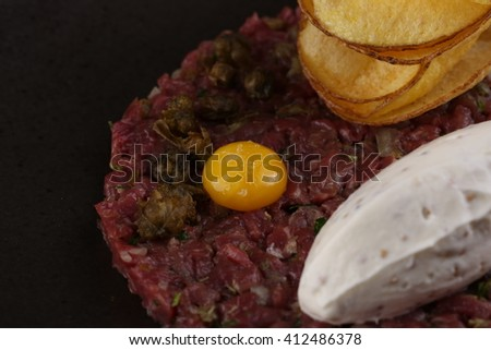 Raw meat small pieces with onion, parsley, egg, tartar sauce, potato chips on a black plate. Closeup.  - stock photo