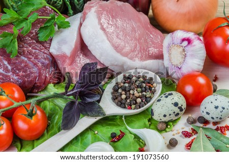 Raw meat, spices and vegetables on rustic wooden board