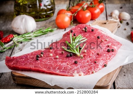 raw meat steak on a cutting board with rosemary and pepper on rustic background - stock photo
