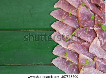 Raw meat steak on dark wooden board. Thin slices of pork. selective focus - stock photo