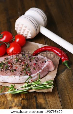 Raw meat steak with spices  herbs, on wooden background - stock photo