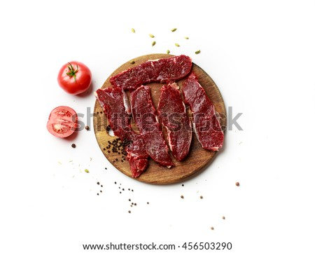 Raw Meat Steaks with tomato and Spices on the wooden board - stock photo