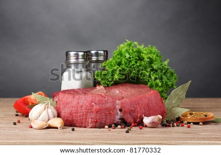 raw meat, vegetables and spices on gray background - stock photo
