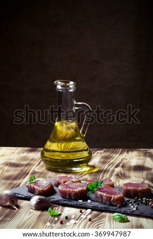 Raw meat with herbs and spices on a black slate plate on a wooden table in front burlap background. Selective focus. Toned.