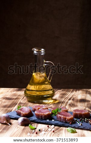 Raw meat with herbs and spices on a black slate plate on a wooden table in front burlap background. Selective focus.