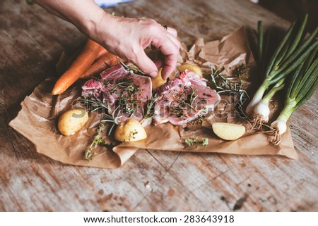 Raw meat with potatoes and herbs on wooden table. Woman hand adding spices  - stock photo