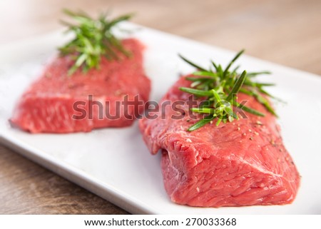 Raw meat with rosemary and pepper - stock photo