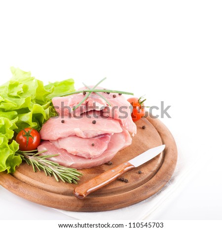 Raw meat with rozmarinom and tomatoes on a wooden board