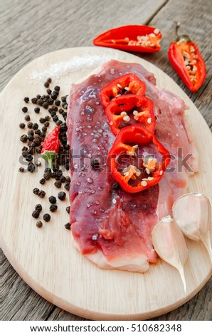 Raw meat with salt, pepper and vegetables on a wooden background. Duck fillet