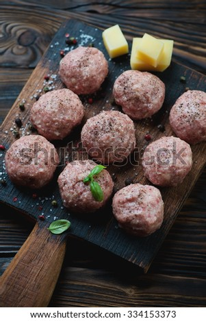 Raw meatballs with spices and parmesan cheese, studio shot