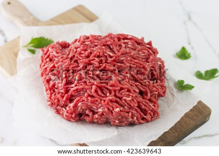 Raw minced beef on wooden background with free space