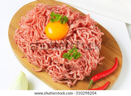 raw minced meat with egg yolk and chili peppers on oval wooden cutting board - stock photo