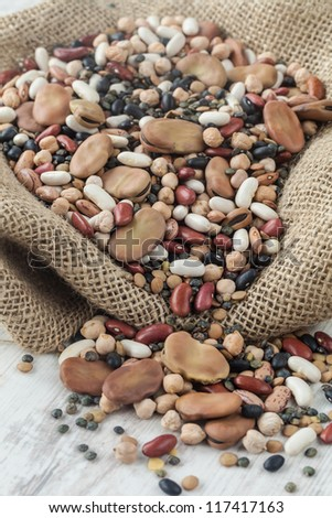 Raw mixed legumes in a jute bag on the table