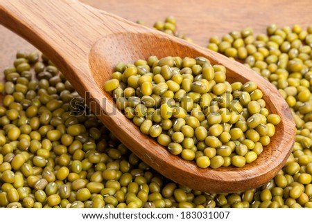 Raw mung beans on wooden spoon in wooden bowl