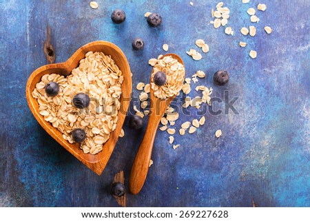 Raw oat flakes with fresh blueberry in heart shaped wooden bowl on blue rustic background. Selective focus - stock photo