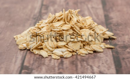 Raw oatmeal over wooden background