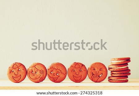raw of cookies with smiley face over wooden table. image is retro style filtered  - stock photo