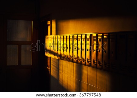 Raw of metal mailboxes in a lobby, sunset light - stock photo