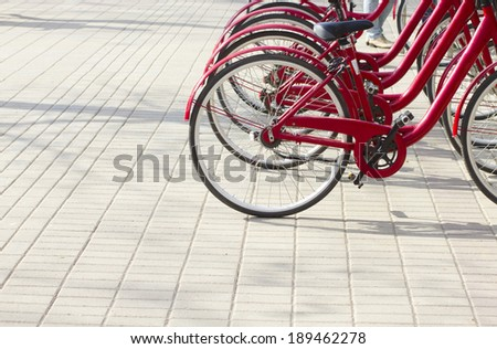 raw of red bicycles for rent, eco city background - stock photo