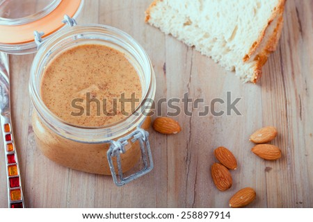 Raw Organic Almond Butter on a wooden rustic Background - stock photo