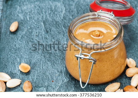 Raw Organic Almond Butter with a few peeled almond on a quartz stone Background.  - stock photo