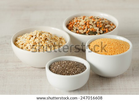 Raw organic amaranth ,chia seeds,oats and other healthy grains in small bowls - stock photo