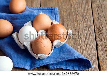 Raw organic brown and white eggs over linen napkin and rustic wooden background - stock photo