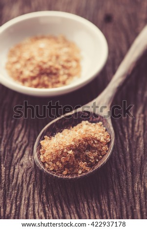 Raw Organic Cane Sugar in a wooden spoon - stock photo