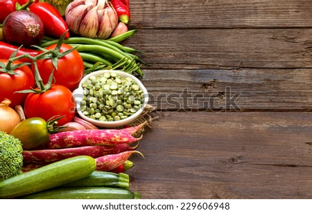 Raw Organic green peas in bowl and vegetables - stock photo