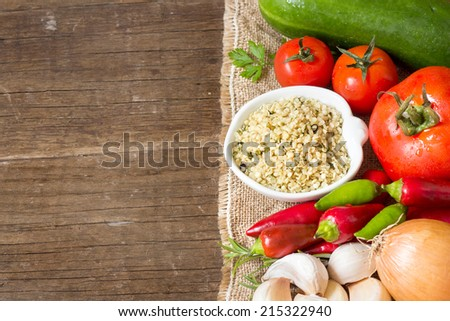 Raw Organic  hemp seeds and vegetables on wooden table - stock photo
