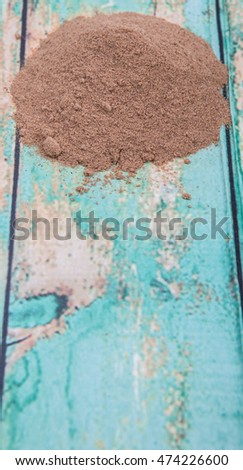 Raw organic super fruit camu camu powder over wooden background