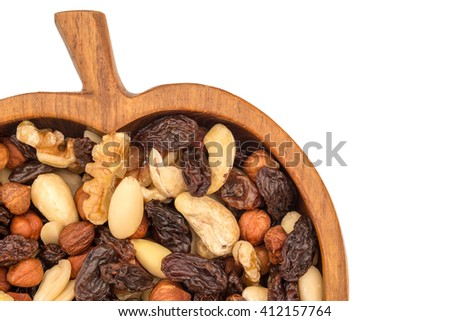 Raw organic trail mix from cashew nuts, raisins, walnuts, macadamia, hazelnuts, brazil nuts, almonds in apple form bowl from olive wood on white background, close up - stock photo