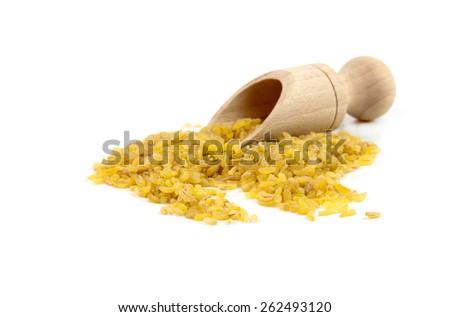 raw organic yellow rice in wooden scoop - stock photo