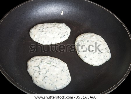 Raw pancakes with herbs on a pan. - stock photo